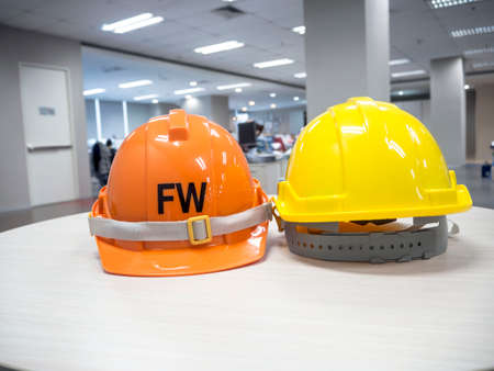head protection: The yellow and orange safety helmet on the table concept security and protection