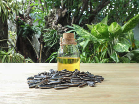 Bottle of Cold pressed sunflower oil with group of sunflower seeds on wooden background, organic product concept