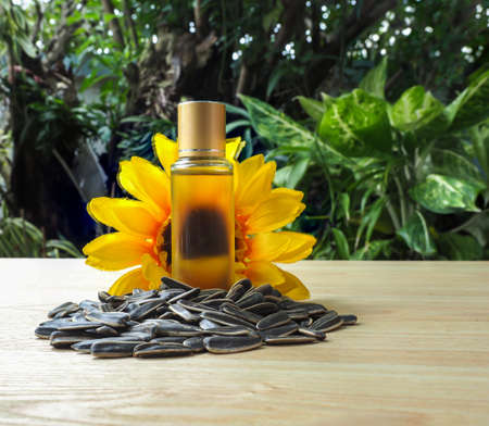 Bottle of Cold pressed sunflower oil in front of sunflower with group of sunflower seeds  on wooden table , organic product concept