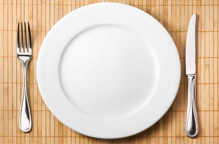 Restaurant serving (metal fork, knife and ceramic white plate) Stock Photo