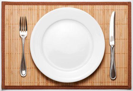 Besteck (Metall Gabel, Messer und keramische weißen Teller) auf Bambus-Matte Standard-Bild - 5834608