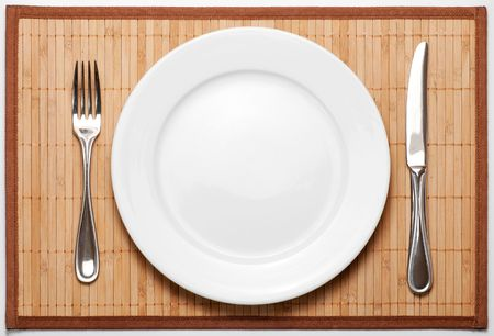 Silverware (metal fork, knife and ceramic white plate) on bamboo mat