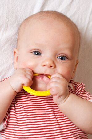 teething: Cute baby with a yellow teething ring Stock Photo