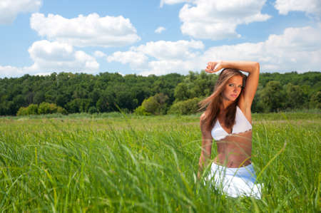Beautiful girl in white dress on green grass