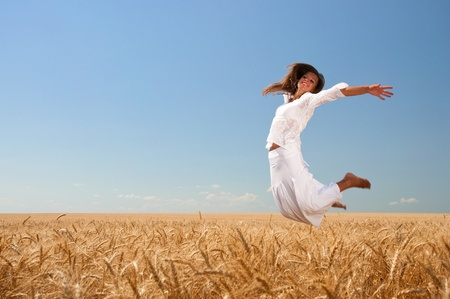 Happy girl in white dress on wheat field photo