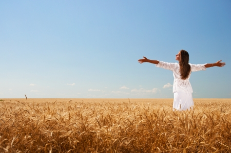 Happy girl in white dress on wheat field photo