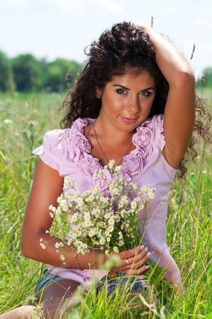 Beautiful girl with flowers on green grass Standard-Bild