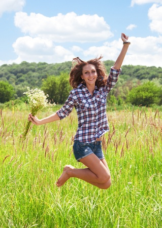 Beautiful happy girl jumping on green grass