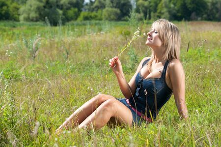 Beautiful happy girl with flower on green grass