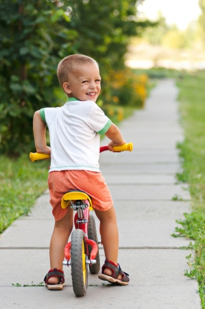 the first step: Little boy riding on his first bike Stock Photo