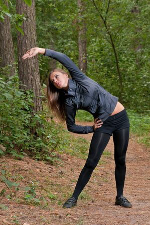 Beautiful girl doing morning exercises in park photo