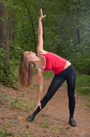 Beautiful girl doing morning exercises in park Standard-Bild