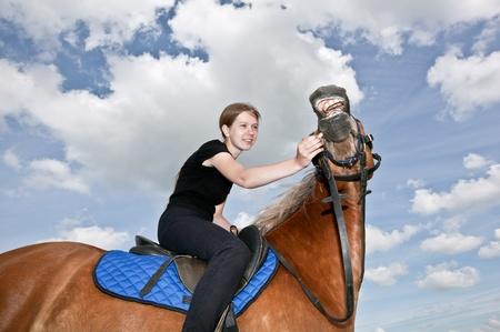 parapente: Chica agradable montar a caballo y la alimentación de un caballo Foto de archivo