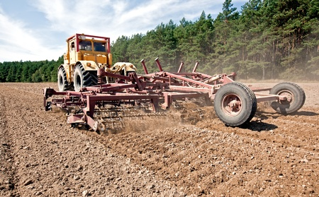 Harrowing a field with a diesel tractor