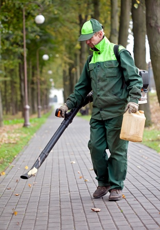 Landscaper cleaning the track using Leaf Blower Stock Photo
