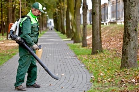 Paisajista operativo gasolina soplador de hojas al limpiar las pistas en el Parque Foto de archivo