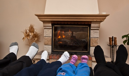Family of Feet warming at a fireplace photo