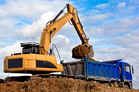 Backhoe loading a dump truck in a quarry 스톡 콘텐츠