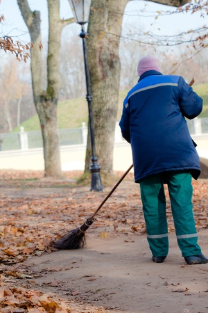 Road Sweeper cleaning walkway in public park from the fallen leaves Stock Photo