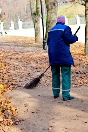 Road Sweeper cleaning walkway in public park from dead leaves