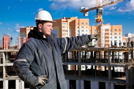 A foreman gives instructions to construction workers at a building site  写真素材