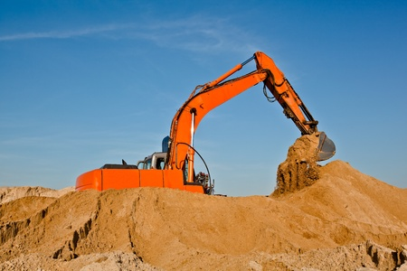 Excavator working in sand pit moving earth by its bucket Stock Photo - 11740910