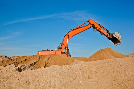 Excavator at sandpit with raised bucket over sky photo