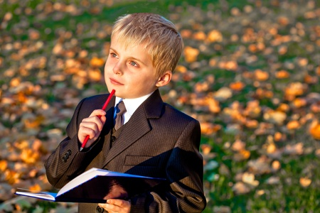 Children little boy pupil with pencil and notebook thinking looking up outdoors