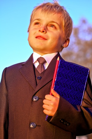 Happy cheerful schoolboy with pencil and notebook on  blue sky background
