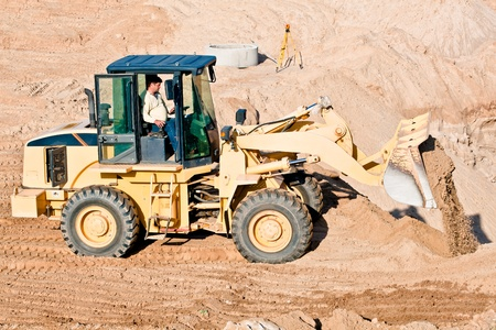 wheel loader: Wheel loader excavator unloading sand during earthmoving works at construction site