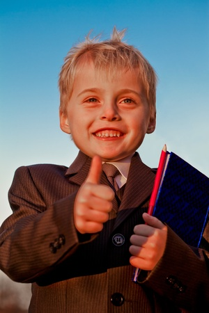 Smiling small pupil in school uniform with pencil and notebook gesturing OK