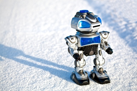 Modern toy combat robot holding his weapon standing on snow Stock Photo - 11740916