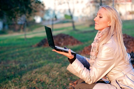 Study time for one young beautiful blonde student girl in autumn park with computer laptop photo