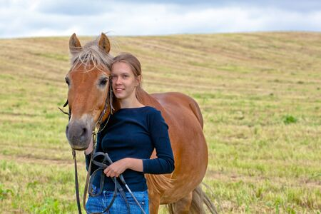 Young cute girl with her horse in a meadow