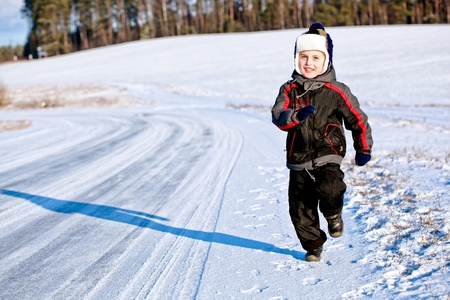 Kid boy running along the road with snow in winter photo
