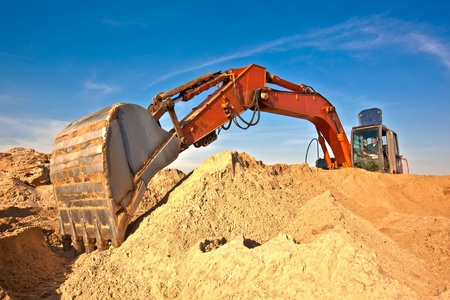 Excavator during earth moving works outdoors at sand quarry photo