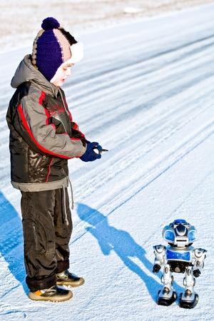 Kid boy playing with toy combat robot on snow photo