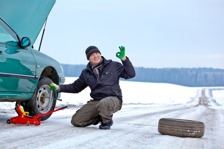Man driver having trouble at road changing wheel repairing car and giving okay sign hand gesture photo