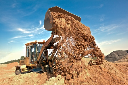 Wheel loader machine unloading soil during earthmoving works at construction site Stock Photo - 11909468