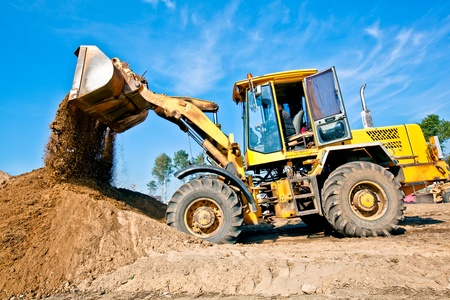 construction workers: Wheel loader machine unloading soil during earthmoving works at construction site