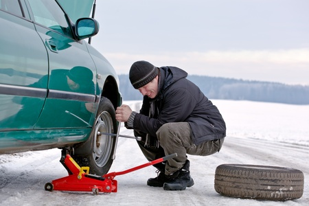 damaged vehicles: Man driver having trouble at the road - changing wheel, repairing car, unscrewing bolts