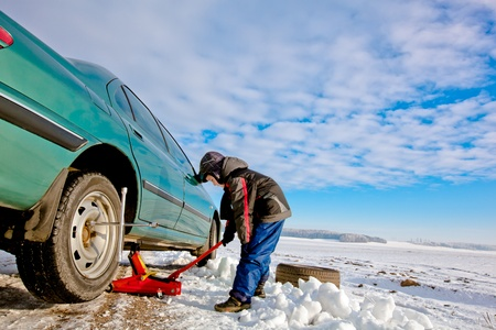 Kid boy helps repairing car, changing wheel, unscrewing bolts Stock Photo - 12192457