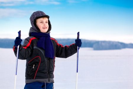 Kid boy skier standing in snow mountain landscape over blue sky, smiles and looks into the distance; horizontal orientation