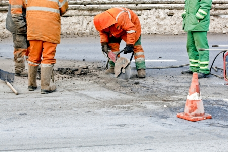 road works: Cutting road works with hydraulic driven angle grinder, upgrading road surfaces; horizontal orientation Stock Photo