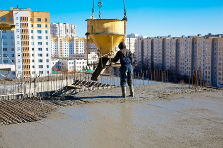 Construction worker pouring concrete during commercial concreting floors and building reinforced concrete structures 写真素材