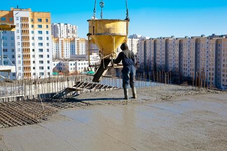 Construction worker pouring concrete during commercial concreting floors and building reinforced concrete structures Standard-Bild