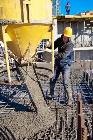 Construction worker pouring concrete during commercial concreting floors and building reinforced concrete structures 스톡 콘텐츠