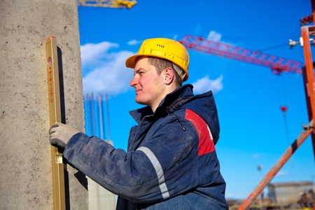 Builder worker with hardhat using water level at construction site during checking vertical level of house wall
