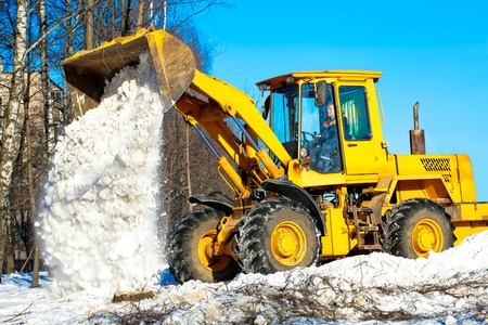 snow clearing: Construction and snow removal equipment at work - wheel loader unloading snow during roadworks