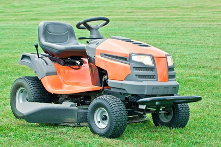 Lawn mower with the lights on against on green grass background 스톡 콘텐츠